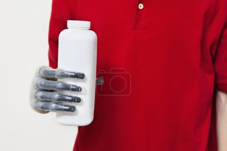 Photo for Mid section of a man holding bottle with prosthetic hand over gray background - Royalty Free Image