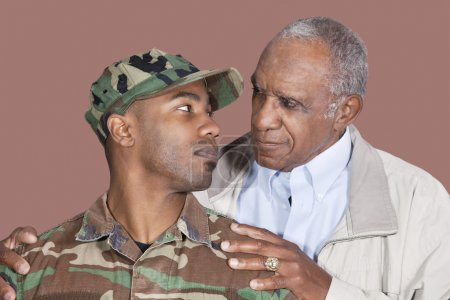 Photo for Father and US Marine Corps soldier looking at each other over brown background - Royalty Free Image