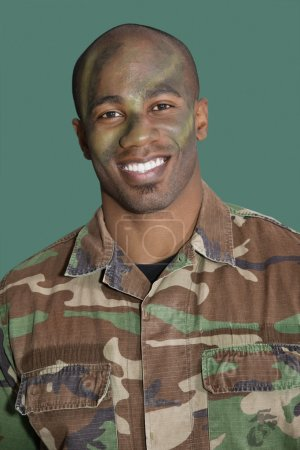 Photo for Portrait of an African American male US Marine Corps soldier with camouflaged face over green background - Royalty Free Image