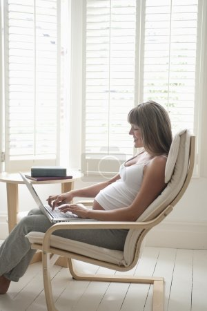 Pregnant woman sitting on chair using laptop