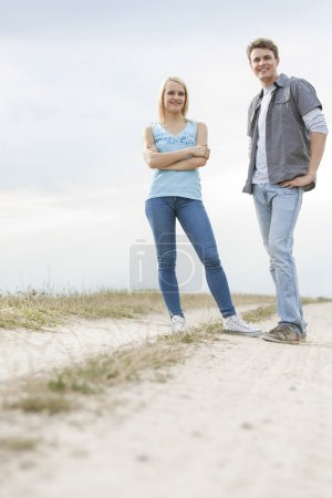 Couple standing on trail at field