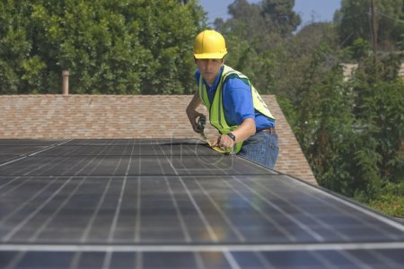 Maintenance worker measures solar array on rooftop