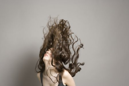 Woman tossing long brown wavy hair