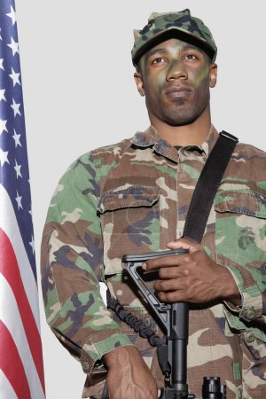 Photo for US Marine Corps soldier with M4 assault rifle standing by American flag over gray background - Royalty Free Image