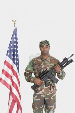 Photo for Portrait of US Marine Corps soldier with M4 assault rifle standing by American flag over gray background - Royalty Free Image