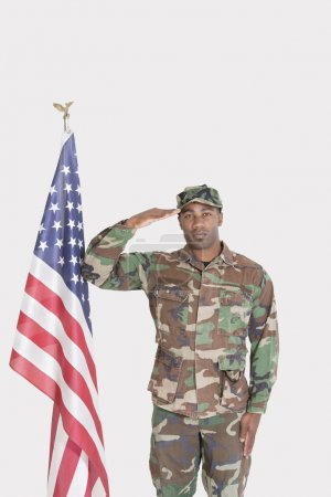 Photo for Portrait of US Marine Corps soldier saluting American flag over gray background - Royalty Free Image