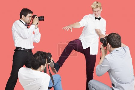 Photo for Paparazzi taking photographs of male actor over red background - Royalty Free Image