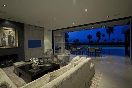 Photo pour Luxueux intérieur avec vue sur piscine et patio, crépuscule - image libre de droit