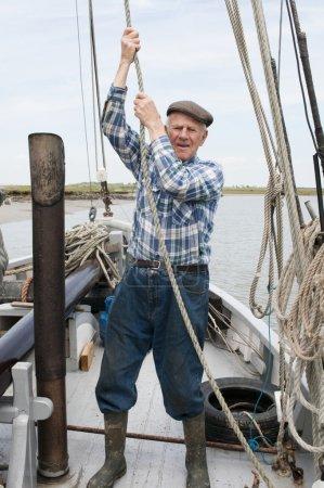 Elderly fisherman pulling rope