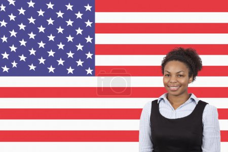 Photo for Young African American businesswoman smiling over American flag - Royalty Free Image