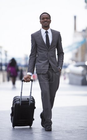 African American businessman pulling suitcase