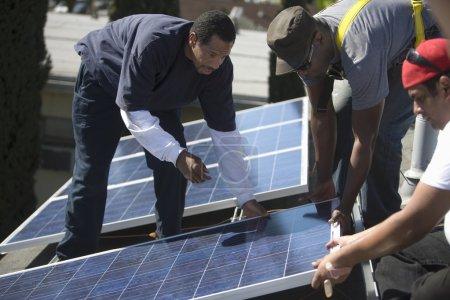 Men lifting a large solar panel