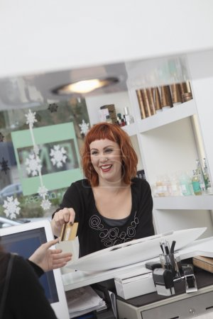 Owner, receptionist takes payment in hairdressing salon