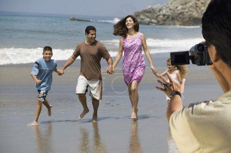 Man video recording Latin family