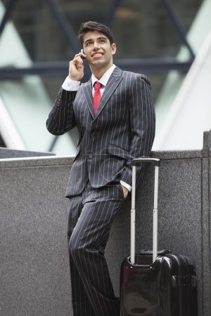 Photo for Young Indian businessman communicating on cell phone while standing next to luggage bag - Royalty Free Image
