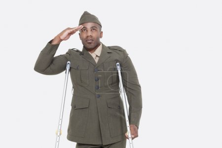 Photo for Disabled African American military officer in uniform salutes over gray background - Royalty Free Image
