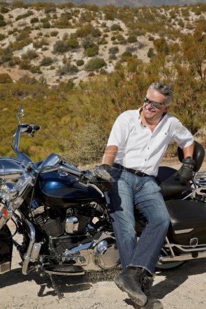 Senior homme se penche sur la moto