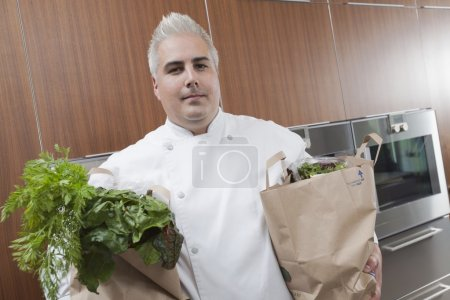 Mid- adult chef with two bags of fresh groceries