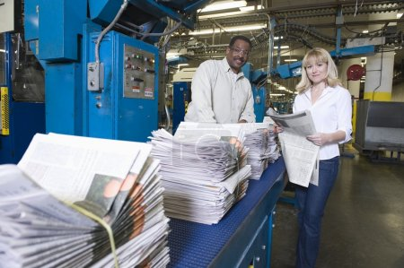 Man and woman on newspaper factory