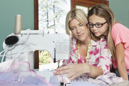 Girl with mother sewing cloth