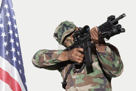 Photo for US Marine Corps soldier aiming M4 assault rifle with American flag against gray background - Royalty Free Image