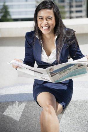 Foto de Retrato de una mujer de negocios india riendo con periódico sentado al aire libre - Imagen libre de derechos