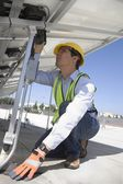 Maintenance worker adjusting solar panel