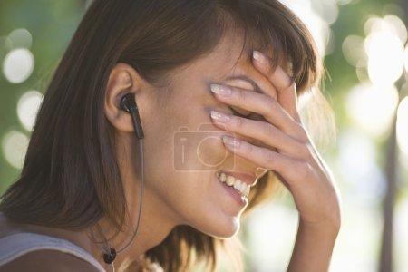 Femme couvre son visage en riant avec un casque