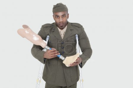 Photo for Portrait of a disabled military officer holding prosthesis leg over gray background - Royalty Free Image