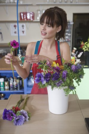 Florist woman arranges flowers