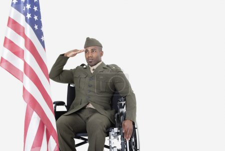 Photo for Young military soldier in wheelchair saluting at American flag over gray background - Royalty Free Image
