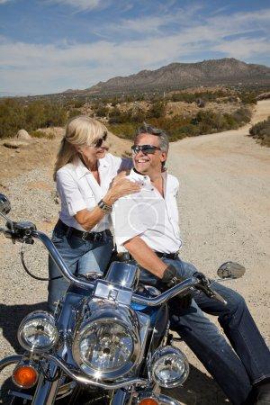 Senior couple sitting on motorcycle