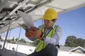 Maintenance worker refers to notes under solar panel