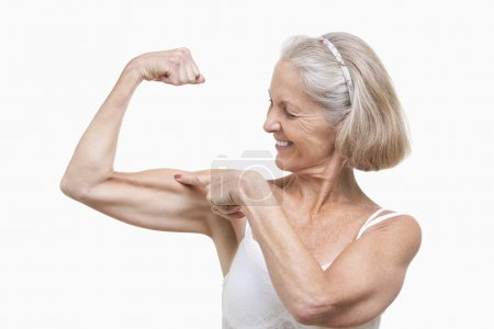 Senior woman flexing muscles