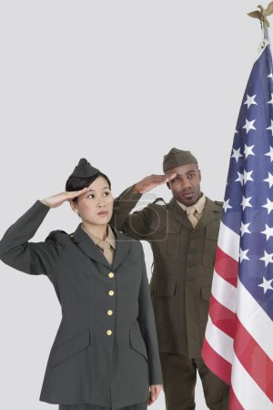 Photo for Multi-ethnic young military officers saluting at American flag over gray background - Royalty Free Image