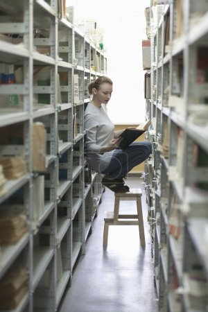 Woman crouches on stool in library