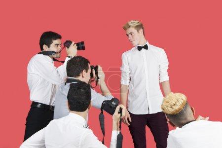 Foto de Paparazzi tomando fotografías de actor masculino sobre fondo rojo - Imagen libre de derechos