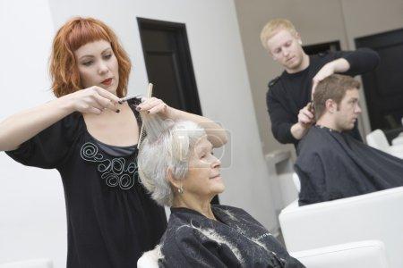 Stylist cuts elderly woman's hair