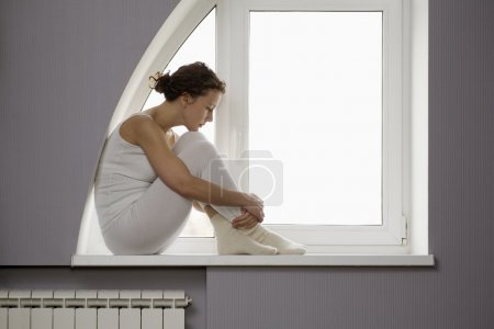 Woman sits on windowsill