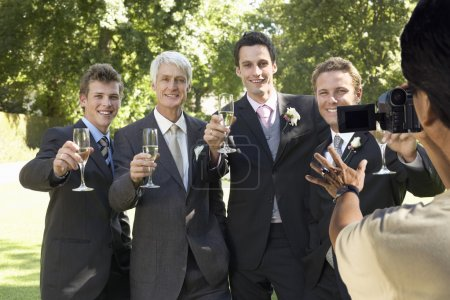 Photo for Man taking a picture of five men toasting with wine glasses at wedding party - Royalty Free Image