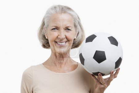 Photo for Portrait of senior woman holding soccer ball against white background - Royalty Free Image