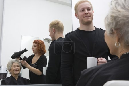 Stylist blow-drys elderly woman's hair  trainee stands with cup