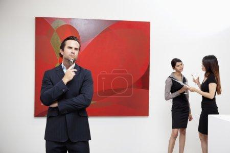 Foto de Joven pensando con mujeres hablando en fondo en Museo - Imagen libre de derechos