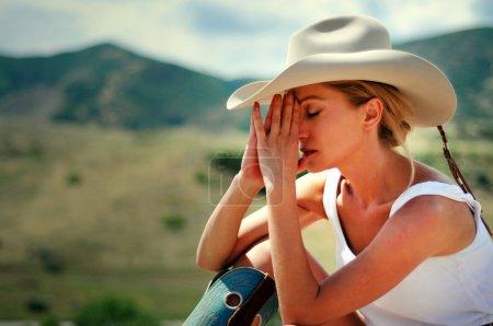Photo pour Jeune femme séduisante slim dans le chapeau de cowboy et bottes assis sur un rocher dans les montagnes - image libre de droit