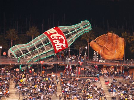 Fans sitting in bleacher section with large glove and giant Coca