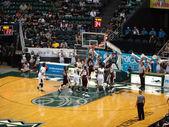 Hráč dunks basketbal jako ostatní snaží zablokovat