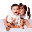 Cute lovely toddler sister hugging happy baby brot...