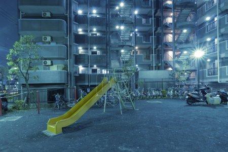 Photo pour Aire de jeux de ville teintée de bleu la nuit près d'un grand immeuble résidentiel - image libre de droit