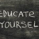 Educate yourself phrase handwritten on school blac...