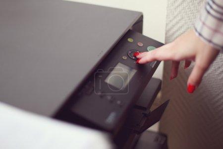 Photo pour Gros plan tige de la main féminine travaillant avec photocopieur - image libre de droit
